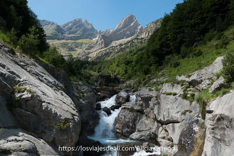 río bajando entre rocas con varios picos puntiagudos al fondo en el Valle de Pineta