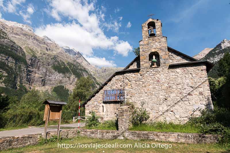 ermita de la virgen de pineta de piedra con pequeña campana y detrás el macizo del monte perdido