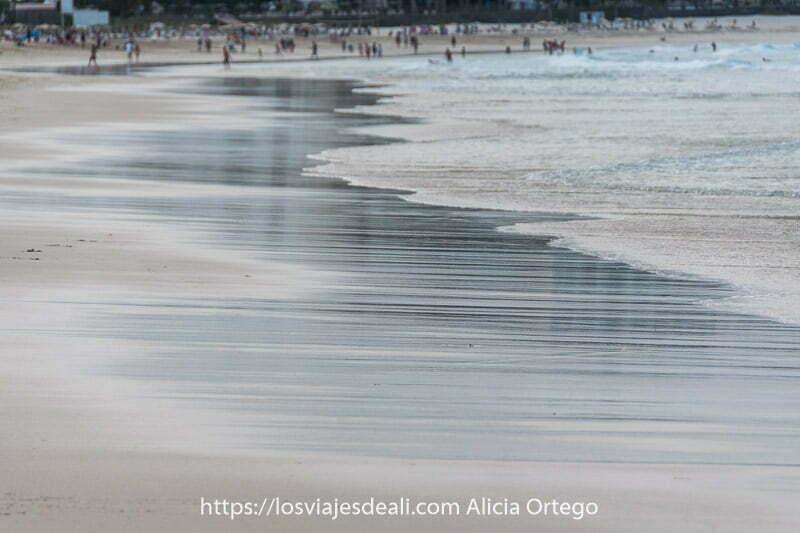 agua retirándose en una playa de fuerteventura y reflejando a la gente