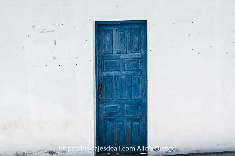 puerta pintada de azul en muro blanco