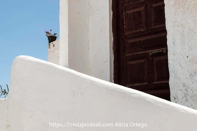 casa de Las Playitas con puerta de madera pintada de oscuro y muros y barandilla de escaleras encaladas