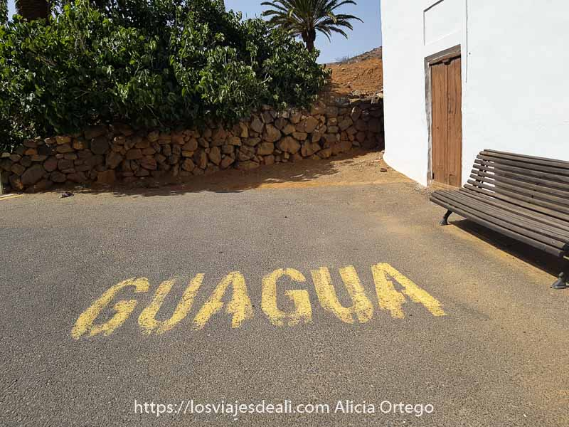 casa blanca con banco de madera y en suelo de asfalto escrito Guagua