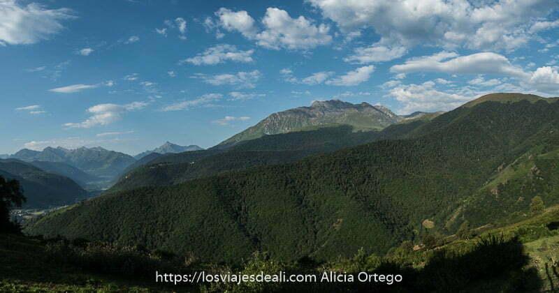 panorámica de montañas cubiertas de bosque y nubes blancas en cielo azul en el pirineo francés