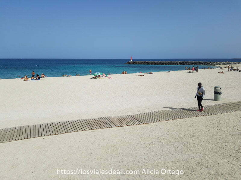 playa chica de puerto del rosario con muy poca gente y un chico africano andando por pasarela de acceso