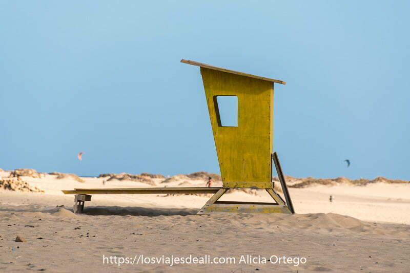 caseta de socorrista de madera pintada de amarillo y unas velas de kitesurf en el horizonte