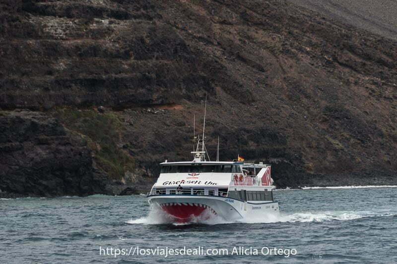 ferry de la isla de la graciosa pasando junto a acantilados volcánicos