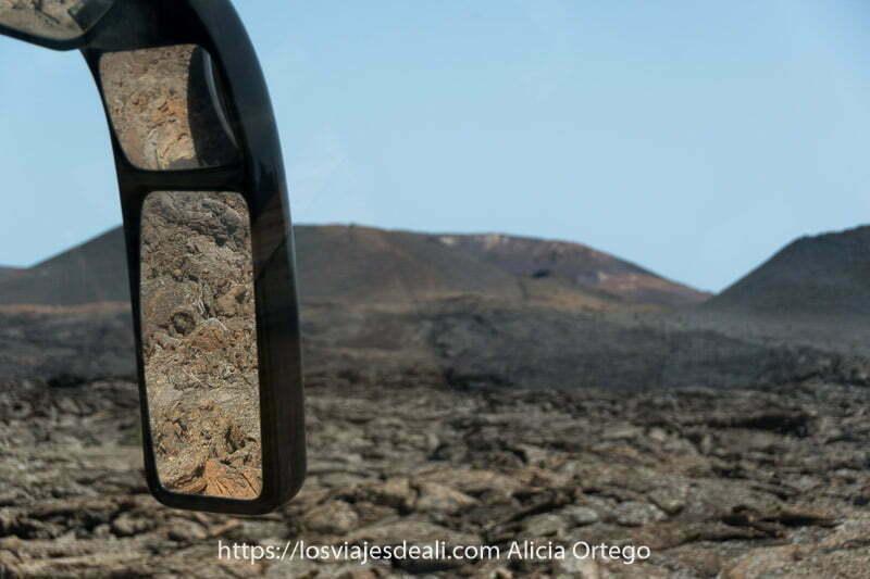 retrovisor del autobús reflejando mar de lava volcánica en timanfaya