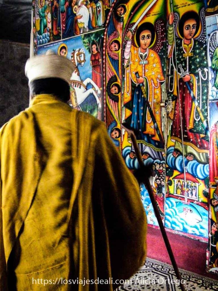recuerdos de etiopía en un monasterio del lago tana con un monje con manto amarillo y gorro blanco y pared llena de dibujos de colores