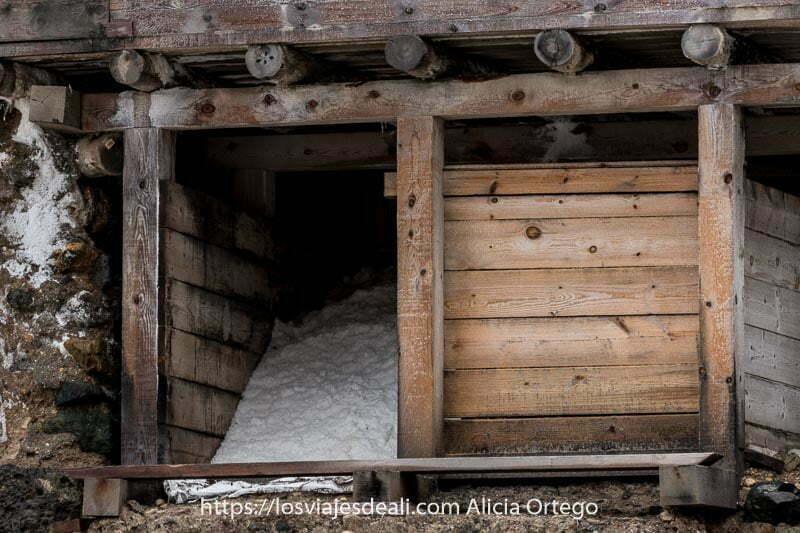 almacén hecho con tablones y troncos de madera lleno de sal