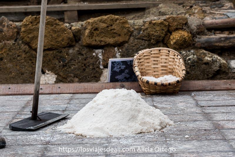 montón de sal sobre era sin agua con cesto tradicional al lado