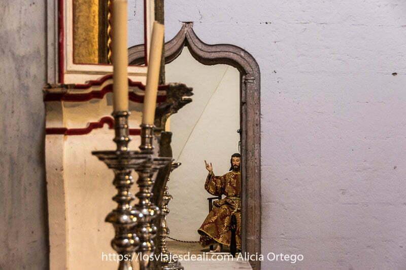 vista del lateral del altar de la iglesia con una puerta al fondo que da paso a otra sala donde hay estatua de jesucristo sentado con mano alzada