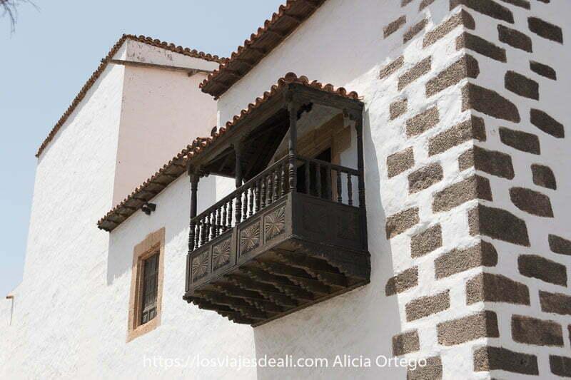 balcón con madera labrada de color oscuro en muro blanco