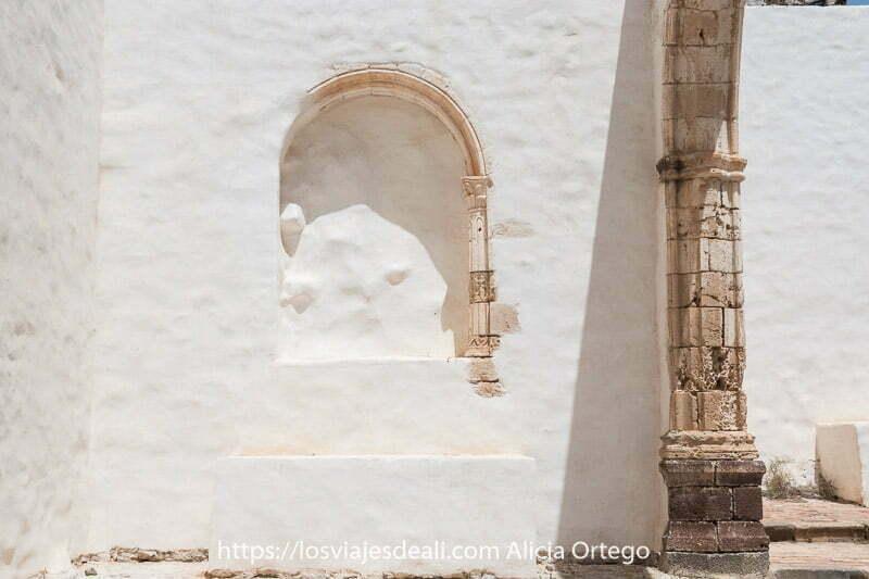 hornacina en la pared blanca con columna de piedra y principio de un arco en la iglesia conventual de betancuria