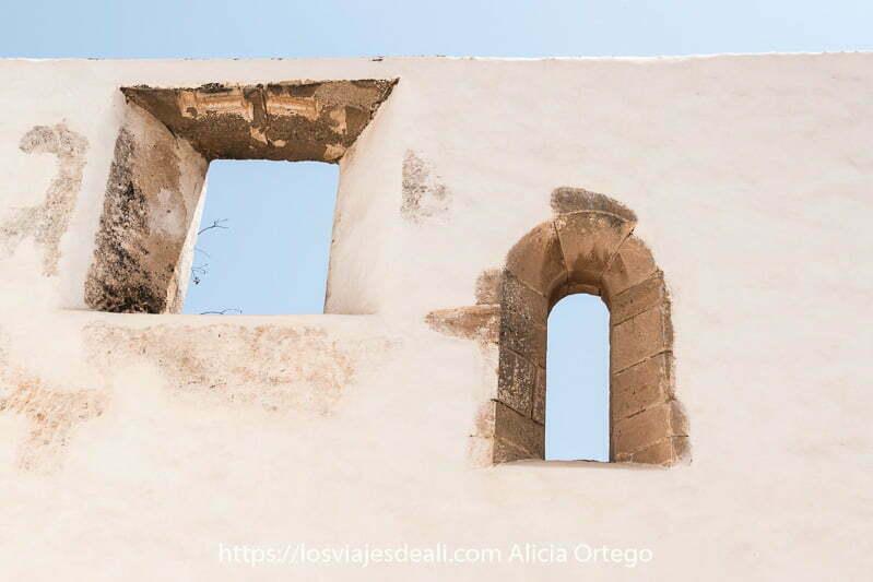 dos ventanas de marco de piedra una cuadrada y otra ovalada en muro blanco y cielo azul