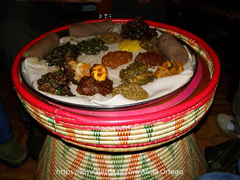 recuerdos de etiopía plato de injera en bandeja redonda sobre soporte de mimbre con decoraciones