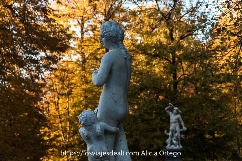 estatua de mujer con niño abrazado a su pierna y fondo de árboles naranjas en otoño en el jardín de la isla de aranjuez
