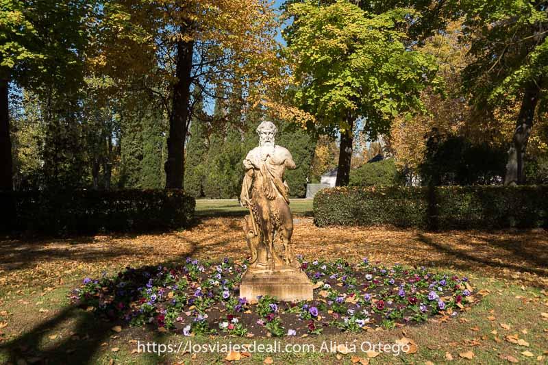 estatua de sátiro rodeado de pensamientos de varios colores en los jardindes del príncipe de Aranjuez