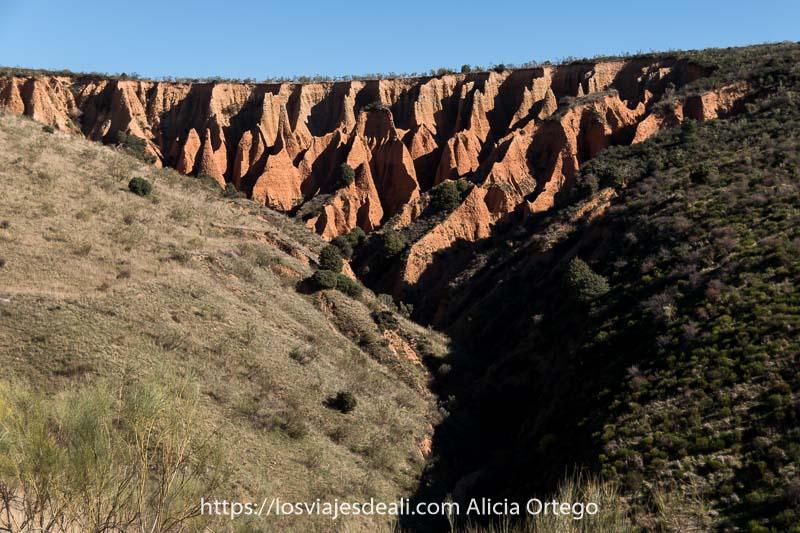 vista de las cárcavas con ladera de montes en forma triangular y cielo azul