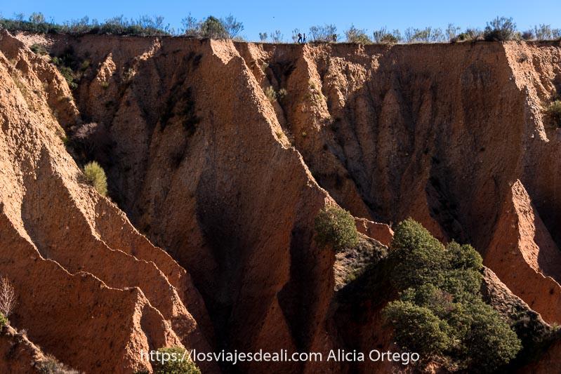 paisaje de las cárcavas y dos personas junto al borde del acantilado que se ven muy pequeñitas