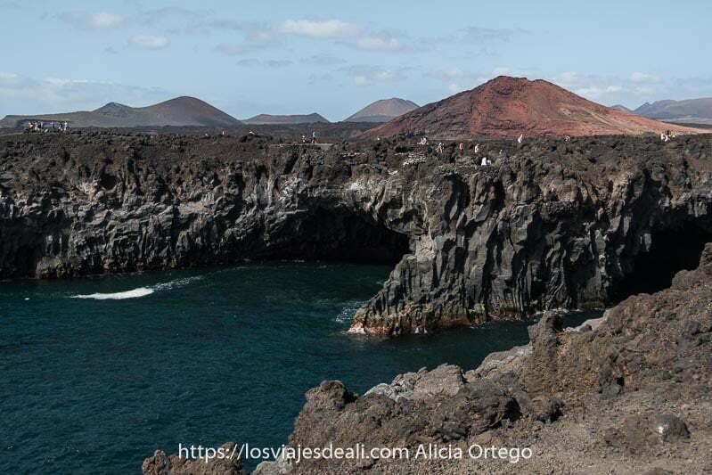 costa de los hervideros con acantilados de basalto y volcanes en el horizonte