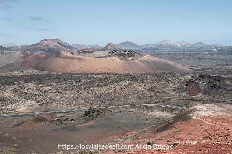 lugares que ver en lanzarote: parque nacional de timanfaya con paisaje lleno de volcanes con colores rojos, amarillos y negros