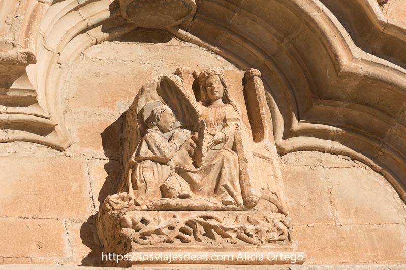 relieve de la iglesia de torrelaguna con una reina sentada en el trono y un monje arrodillado ante ella