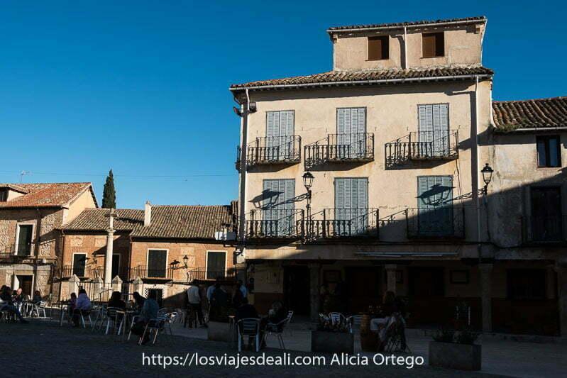 casa de torrelaguna con 6 balcones con persianas de color azul y terraza con gente tomando algo delante