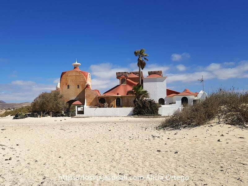 casa de estilo Dalí con una palmera en el centro en la playa de la Concha de El Cotillo