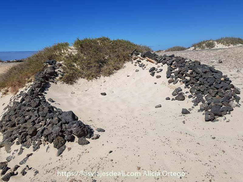 corralillo hecho con piedras volcánicas en una playa de El Cotillo