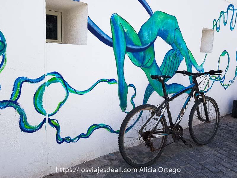 mural en pared blanca con una mujer haciendo gimnasia rítmica contorsionándose sobre aro en colores azul y verde y bicicleta aparcada