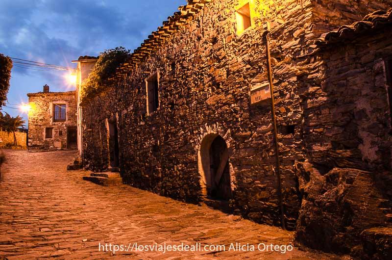 calle de patones de arriba con casas de piedra y calle adoquinada con farolas encendidas