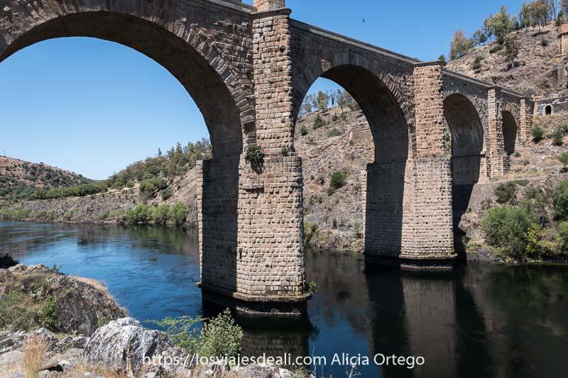 puente de alcántara con sus pilares sumergidos en el río tajo y las orillas escarpadas