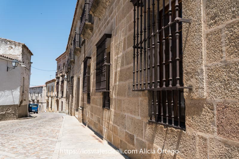 calle con fachada de convento con rejas en las ventanas