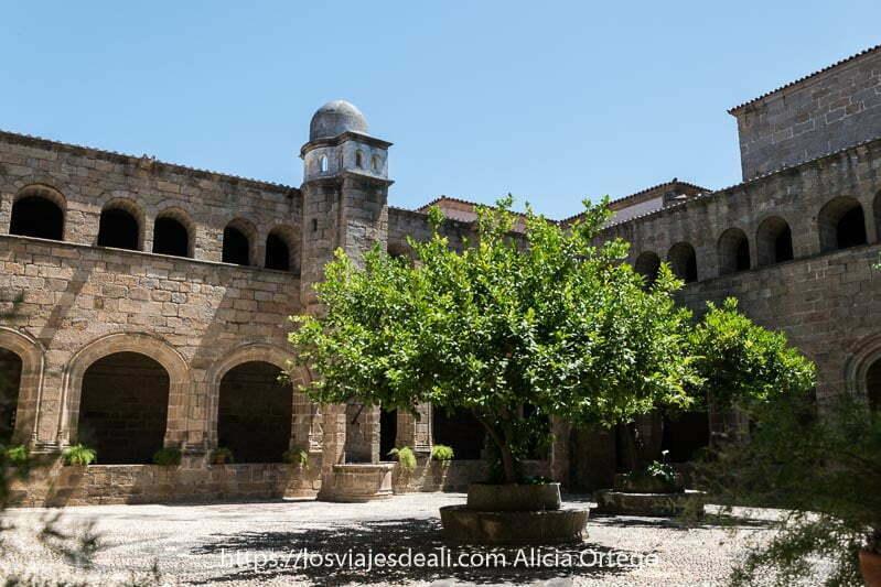 claustro del conventual de san benito con dos áboles en el centro y torre con pequeña cúpula