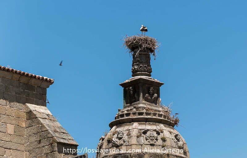 torre de piedra terminada en cúpula con mucha decoración y arriba un nido con una cigüeña de pie