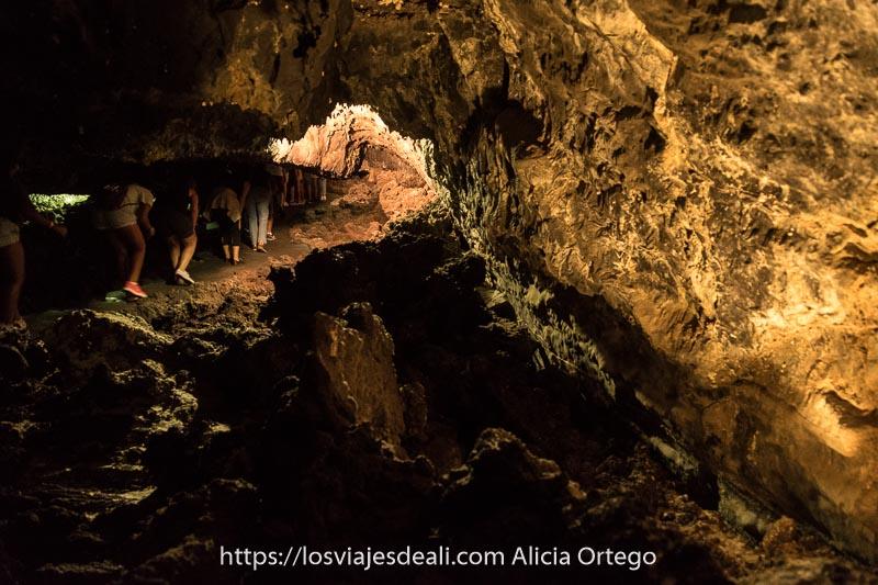visitantes andando agachados en ángulo de 90 grados en la cueva de los verdes