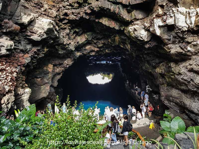 laguna de los jameos bajo gran techo de piedra natural y mucha gente mirando al agua