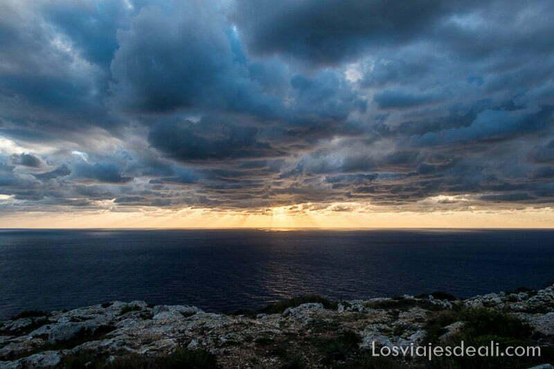 atardecer en los acantilados de Dingli con grandes nubes y rayos de sol en el horizonte