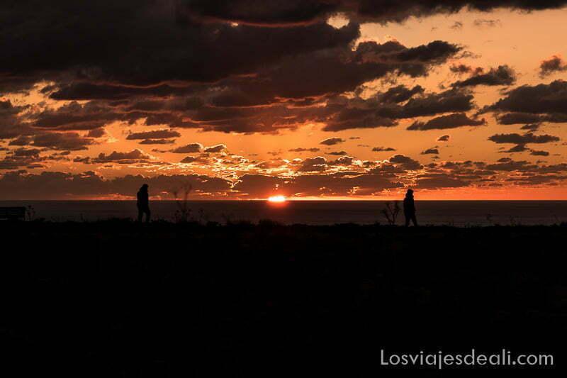dos personas andando en los acantilados con el sol entre ellas y nubes