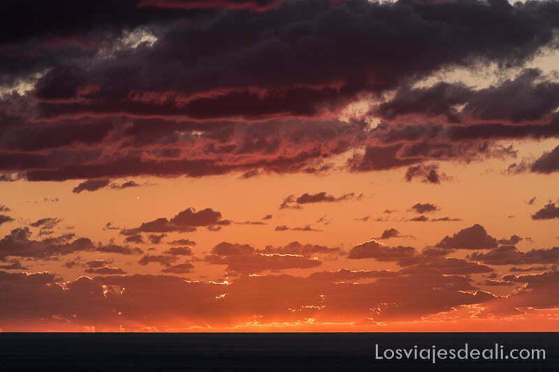 nubes coloreadas con rojo y rosa con el mar en la parte inferior