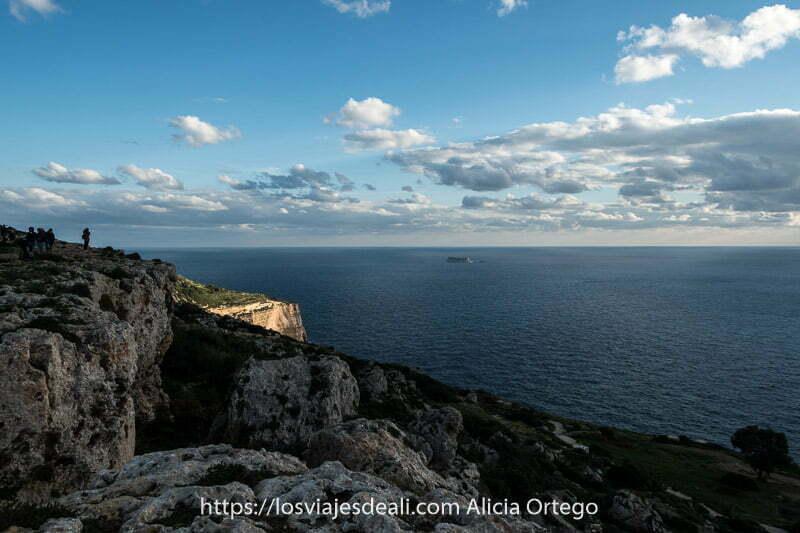 costa con acantilado iluminado y la isla de filfla enfrente enmedio del mar