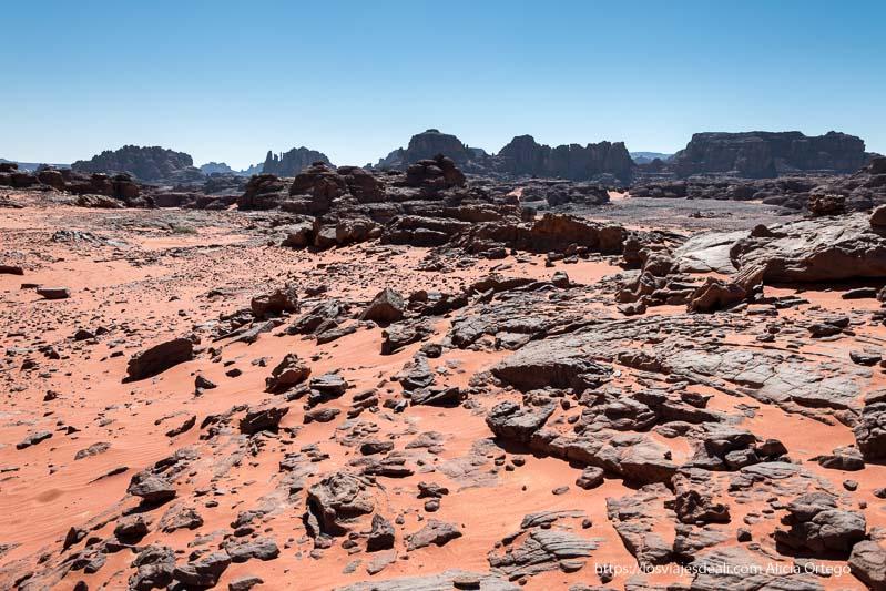 paisaje con mesetas basálticas al fondo y rocas negras entre arena roja en primer plano