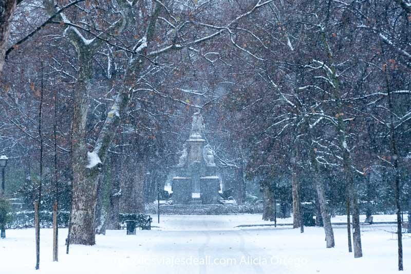 estatua al fondo de un camino entre árboles en el retiro mientras nieva