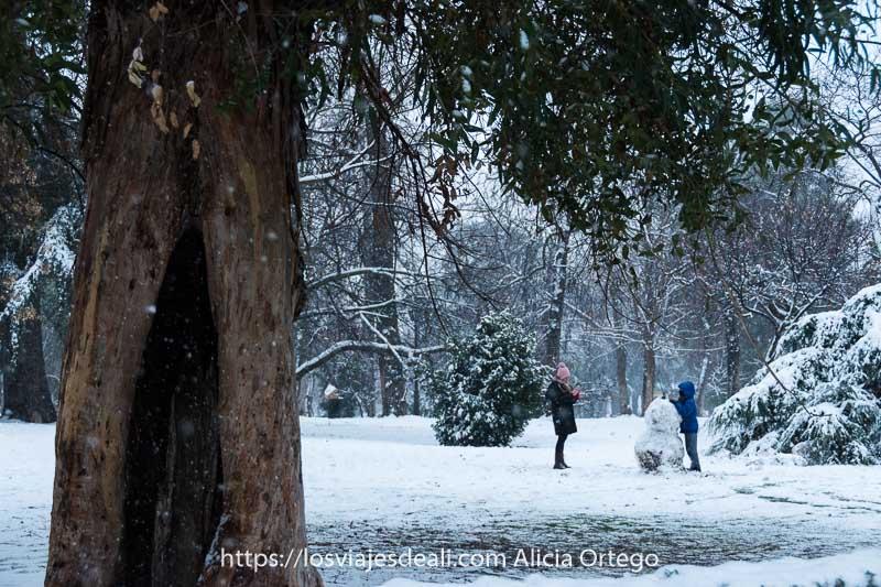una chica con gorro rosa y un niño con chaqueta azul haciendo un muñeco de nieve en el retiro