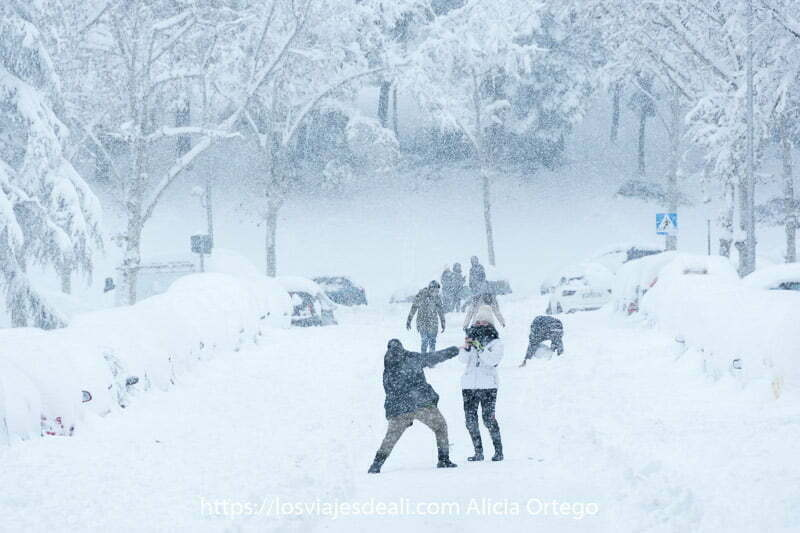 personas haciéndose fotos y muñecos de nieve en medio de la calzada de coches todo llenísimo de nieve y con copos cayendo
