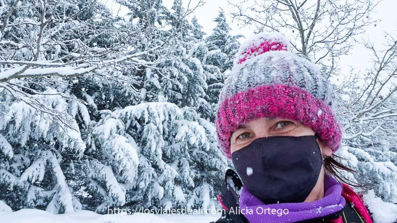 selfie con gorro de lana rosa y gris y ramas de árboles llenos de nieve detrás