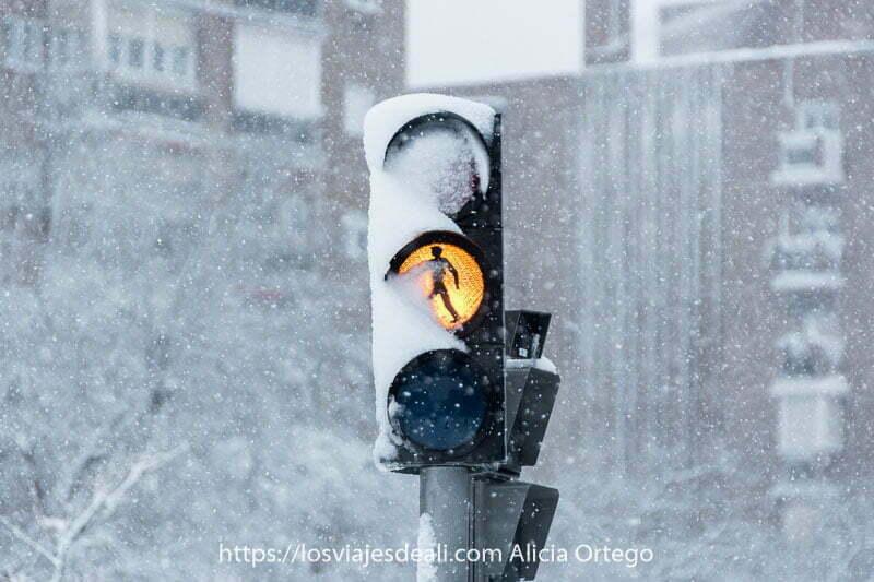 semáforo con luz ámbar encendida con mucha nieve en madrid