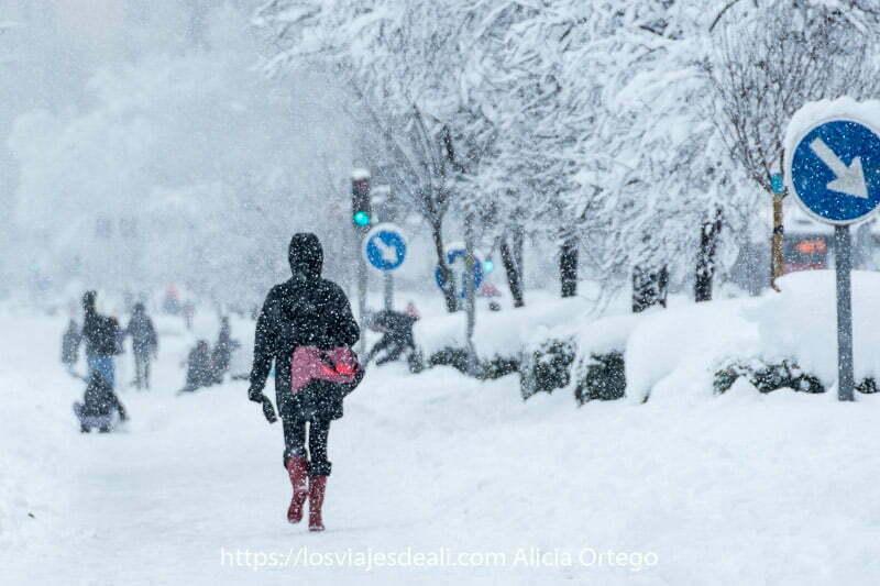 mujer andando con bolsa y botas rojas en una calle durante la gran nevada