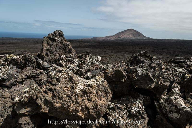 lavas alzadas con volcán en el horizonte y mar de lava negra en la ruta de la caldera blanca