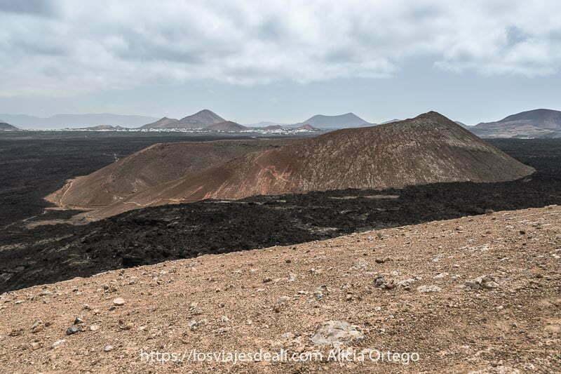 vista de la caldera pequeña desde arriba en color rojizo enmedio de un campo de lava negra